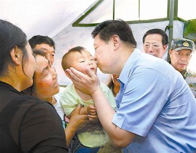 2013年5月21日,习近平在芦山县体育馆安置点一帐篷内亲抚一小孩。