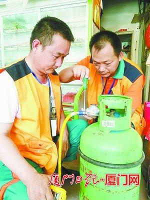 安检员在为瓶装液化气安装减压阀和金属软管。