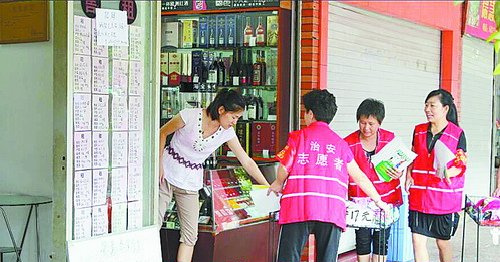 在兴华社区,平安志愿者和路长正在劝导商家收起违规摆放的货架。
