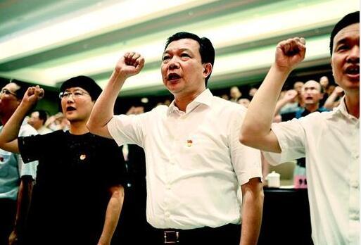 圖為今年7月1日,武漢市委組織部機關黨課前,楊漢軍(右二)握拳宣誓。他用生命踐行入黨誓詞,把一切獻給黨。 (資料圖片)