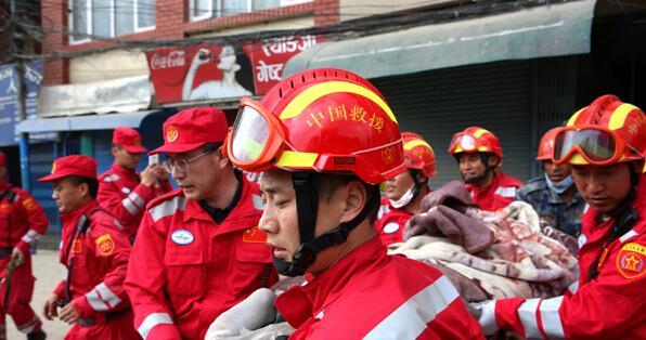 在尼泊尔首都加德满都,中国国际救援队搜救队员从因地震坍塌的楼房中抬出一名幸存者