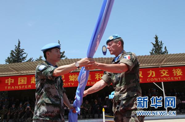 在黎巴嫩南部辛尼亚村的中国营举行的中国赴黎维和部队轮换交接仪式上,联合国驻黎巴嫩临时部队(联黎部队)参谋长皮埃尔(右)将联合国旗交到中国第16批赴黎维和部队指挥长黄云手中