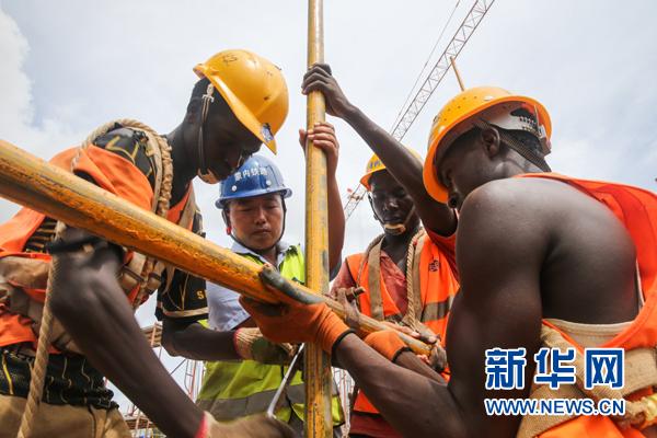 在肯尼亚蒙巴萨,中国工程师张青春(左二)和肯方工人们在蒙内铁路蒙巴萨西站工地上工作。蒙内铁路由中交集团总承包,中国路桥承建,连接东非最大港口蒙巴萨和肯尼亚首都内罗毕