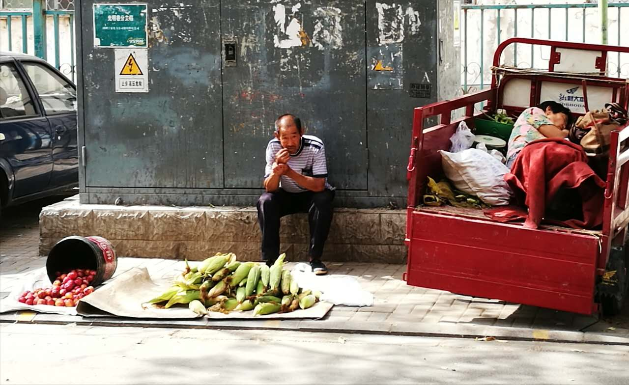 Man who is selling home-grown corn and tomatoes on street. (Photo/ Wang Yabo)