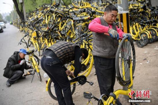 资料图:工作人员正在修理仍可修复的单车。 中新社记者 崔楠 摄