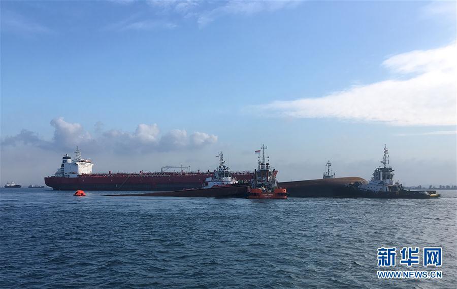 9月13日,四艘拖船将部分淹没的挖沙船转移至新加坡安乐岛附近海域,以便进行水下搜索活动。新华社发(新加坡海事及港务管理局供图)