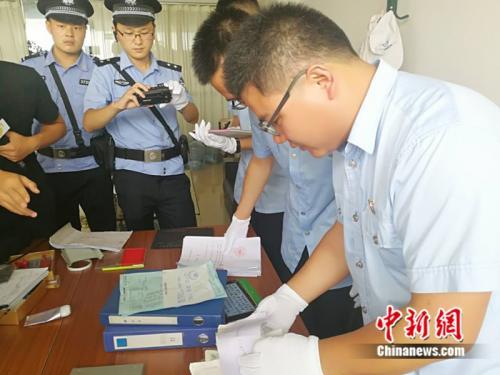 """资料图:法院执行人员在现场搜查""""老赖""""财务账本。 中新网记者 张尼 摄"""