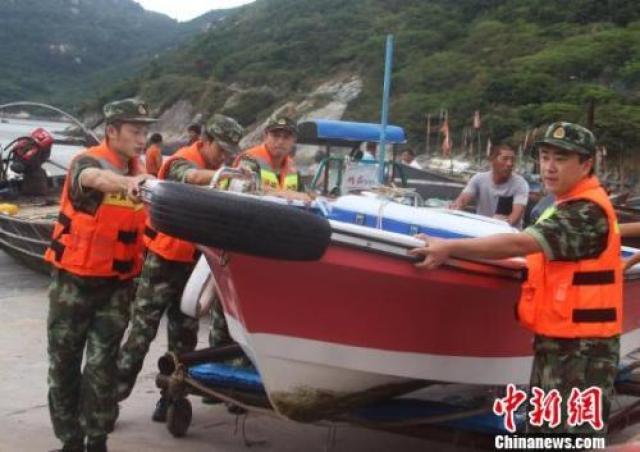 图为温州公安边防官兵帮民众转移船只。王华 摄