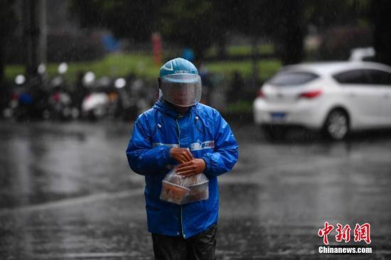 资料图:外卖小哥冒雨送餐。中新社记者 刘冉阳 摄