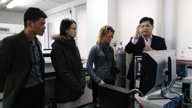 2017年1月,朱永官(右一)在实验室向《Science》记者讲述该研究成果。中科院城市环境研究所供图。