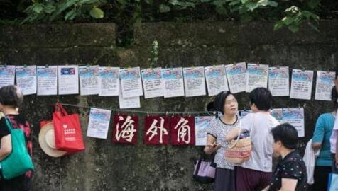 """资料图:2017年7月15日,杭州一条马路两边,数百名大伯大妈前来""""相亲"""",现场还特别设置了海外学子的专区,贴着的大部分都是70后80后年轻人的信息"""