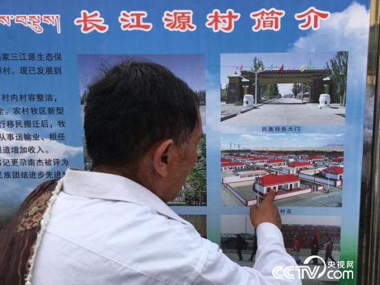 更尕南杰走过村口的长廊,长廊中张贴着总书记视察长江源村的图片。