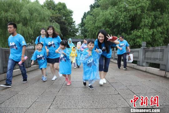 """30个龙凤胎家庭23日穿着统一的""""大熊猫纪念T恤"""",为""""月月半半""""公益跑。(倪丽 摄)"""