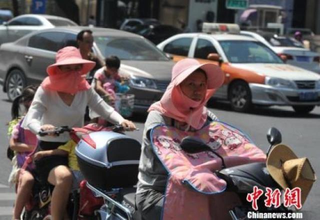"""图为福州市民出行""""全副武装""""防晒。"""