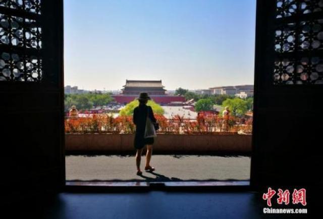 资料图:9月,北京进入秋高气爽时节,图为故宫博物院工作人员在故宫内穿行。
