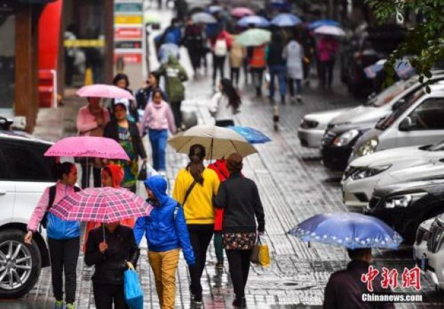 9月24日,新疆乌鲁木齐市降下秋雨,外出民众打着雨伞快步前行。