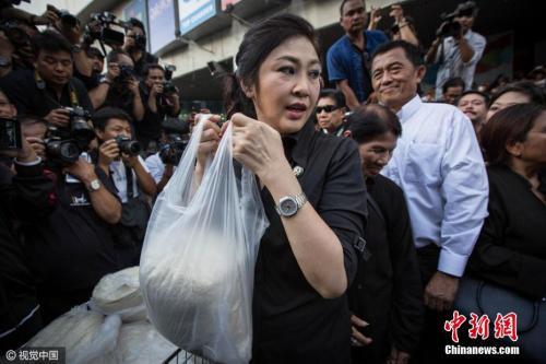 当地时间2016年11月11日,泰国曼谷,因米价下跌农民大受打击,泰国前总理英拉现身街头亲自帮助米农卖大米,声援米农。图片来源:视觉中国。