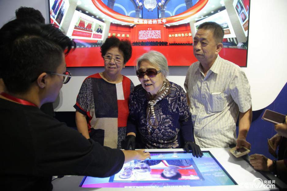89岁老人王志强与家人在电子屏前为喜爱的展区点赞