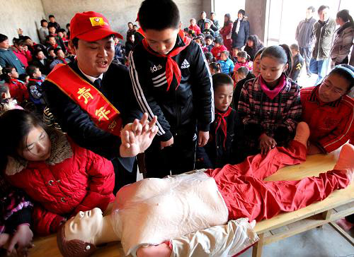 (A volunteer is showing pupils first-aid operations in electricity shocks Photo from Xinhua)
