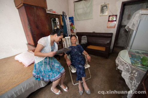 (A volunteer is reading newspaper to a 83-year granny  Photo from Xinhua)