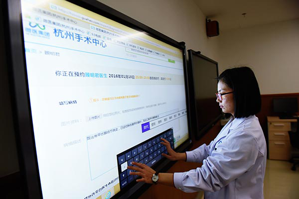 (A member of medical staff operates big-screen online diagnostic equipment at a medical center in Hangzhou, capital of Zhejiang province. Photo/Long Wei from China Daily)