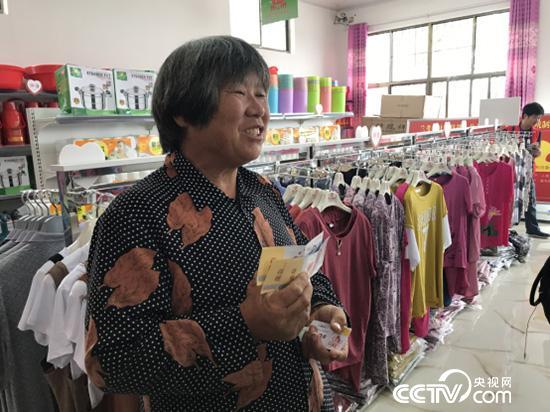 黄兰各拿着爱心卡将在超市兑换大米。(记者 王莉莉 摄)