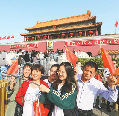 10月1日,来自黑龙江的游客在北京天安门前拍照留念。国庆长假第一天,天安门广场地区迎来大批游客。王 振摄(人民视觉)