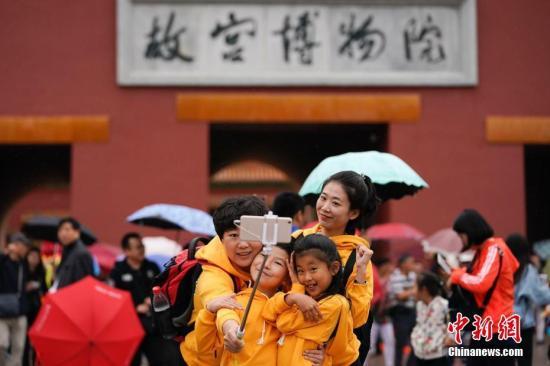 10月2日,北京小雨,游客在故宫博物院游览。中新社记者 杜洋 摄