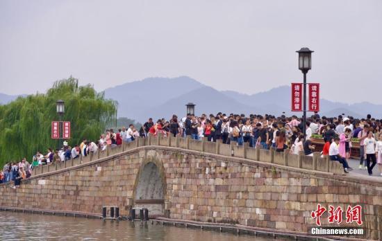 10月3日,国庆长假第三天,大量游客涌入西湖断桥。据了解,为更好地引导游客有序游览,西湖断桥被花箱隔离栏纵向一分为二,并设置了一进一出两条单行线。