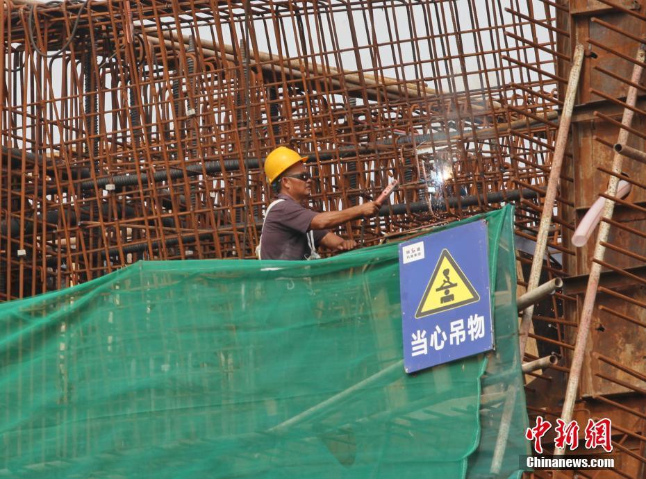 建设者在四川眉山市东坡区岷江一桥改造工程施工现场忙碌。