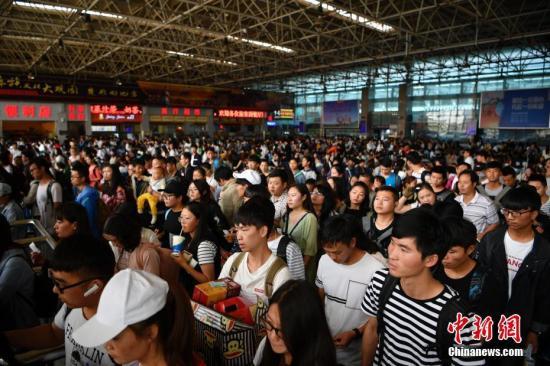 10月1日,旅客排队乘车。当日是国庆长假第一天,昆明火车站迎来出行高峰,客流以旅游、探亲为主。