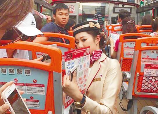 大陆游客乘坐台北观光大巴,使用手机支付采买纪念商品。