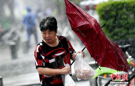 资料图:福州市民顶风出行。