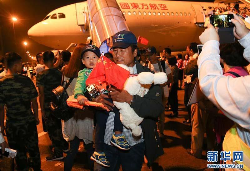 10月1日晚,在上海虹桥机场,飓风受困同胞走下飞机前往摆渡车。两架东航包机飞越19国,接回此前在加勒比岛国多米尼克遭遇飓风受困的同胞。新华社记者 丁汀 摄