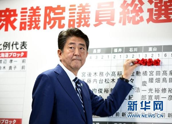 10月22日,在日本东京自民党总部,日本首相、自民党总裁安倍晋三为当选议员贴花。