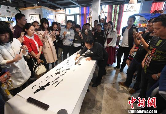 台湾少数书法家谢石鸿现场挥毫题写书法作品,引书法爱好者围观。