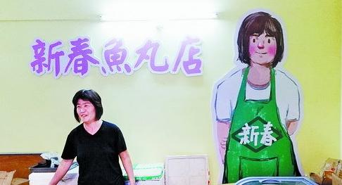 """一家鱼丸店的墙壁上画着自家老板娘,大大的卡通形象满面微笑,很是讨喜。""""画得很好,我很喜欢。这些设计者像我的孩子一样。""""老板娘施女士说。"""