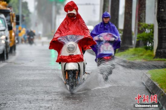 """资料图:10月15日,海口民众雨中涉水骑行。今年第20号台风""""卡努""""台风级当日上午开始影响海南,海口市区出现强降水天气。中新社记者 骆云飞 摄"""