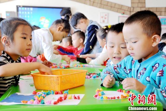 资料图:9月8日,第33个教师节来临之际,甘肃张掖民乐县第一幼儿园大班的小朋友为老师制作爱心卡片,用自己的亲手劳动为老师们送去节日的祝福。 张渊 摄