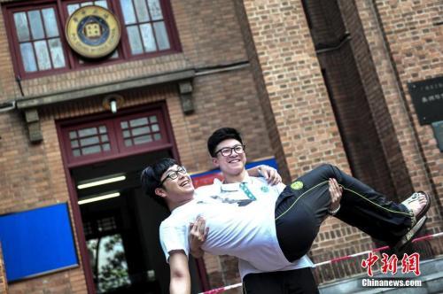 资料图:一名高考考生抱起同学在考场前合影留念。中新社记者 陈骥旻 摄