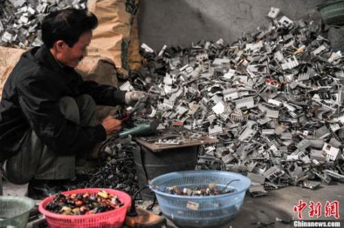 资料图:2013年4月8日,广东汕头贵屿镇上一名工人正在分拣电子元件。