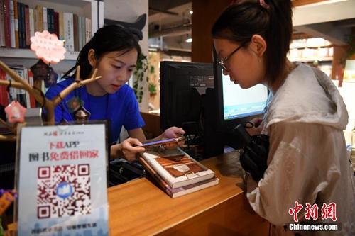 """资料图:书店工作人员帮读者办理共享图书借阅。安徽省合肥市新华书店三孝口店""""变身""""为共享书店,读者只需缴纳99元押金就可免费把书从书店带回家阅读。"""