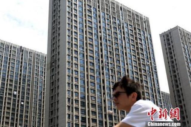 ↑资料图:市民从南京一处楼盘前经过。
