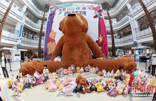 资料图:一只高度达20米的毛绒玩具熊在山西太原一大型商场亮相,吸引了众多市民前来观看。