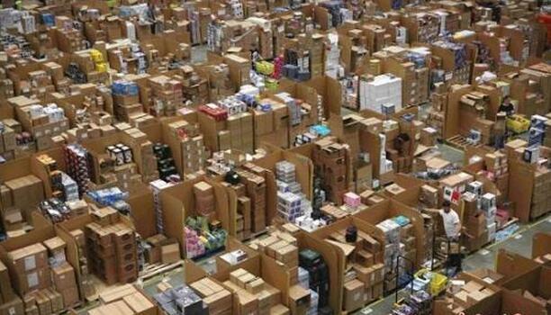 """资料图:""""黑五当天"""",英国的一处亚马逊仓库内,工作人员正忙着给商品装箱。"""