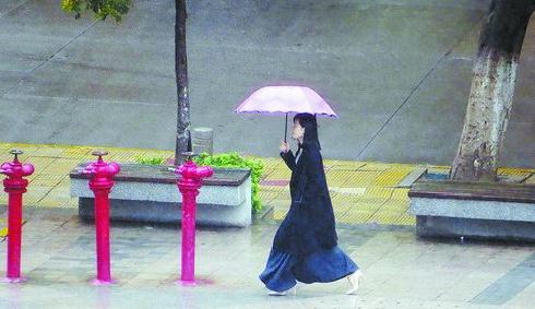 ▲前日,厦门阴雨寒冷。图为25日雨中行人