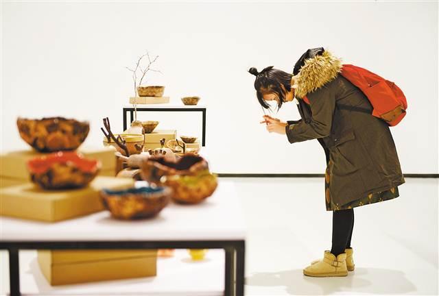 11月25日,四川美术学院虎溪校区罗中立美术馆,设计介入精准扶贫案例展现场。游客正在《传统工艺新生》展台拍摄艺术品。