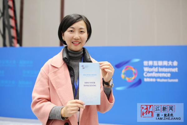 志愿者张潘丽展示第四届世界互联网大会手册。
