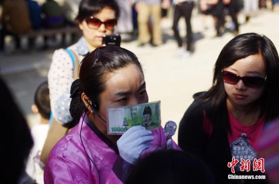 资料图:韩国首尔景福宫内一位汉语导游正向中国游客介绍韩文的由来。 中新社发 贾天勇 摄