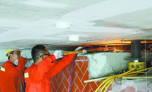 工人在拆除旧的桥梁支座,一旁的黄色机器为千斤顶。